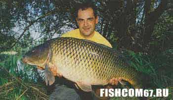 Рыболов с огромным карпом в руках