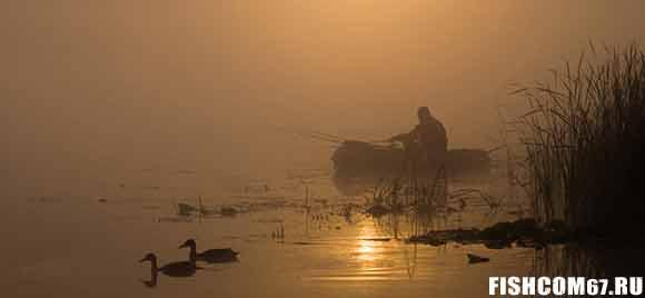 Рыболов на лодке в тумане